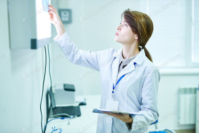 Doctor standing and looking at X-ray