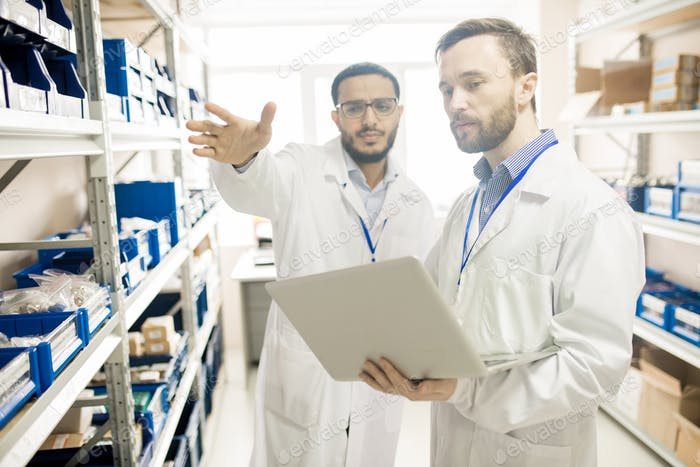 Busy factory lab technicians keeping records of devices