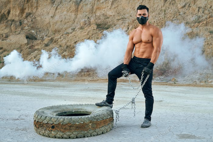Bodybuilder with naked torso standing near tyre at sand pit