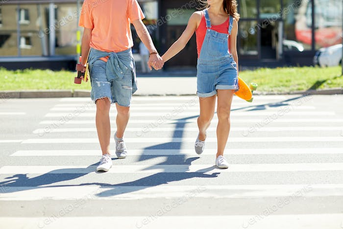 teenage couple with skateboards on city crosswalk