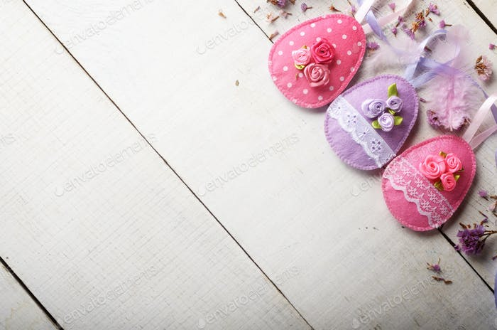 Handmade patchwork pink and lilac felt easter eggs on white wood