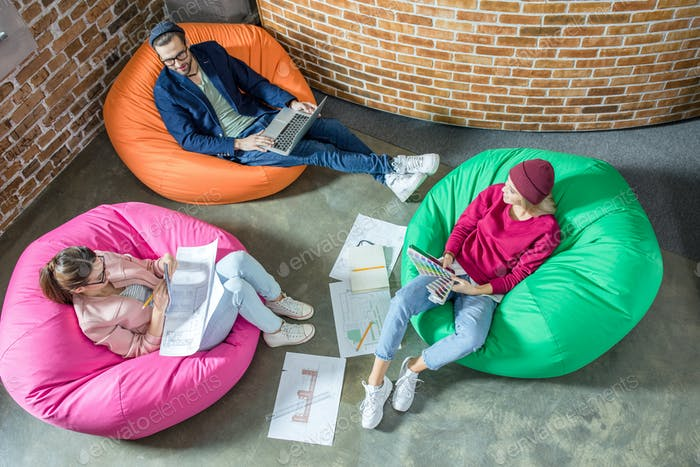 Top view of young designers or architects working while sitting in bean bag chairs