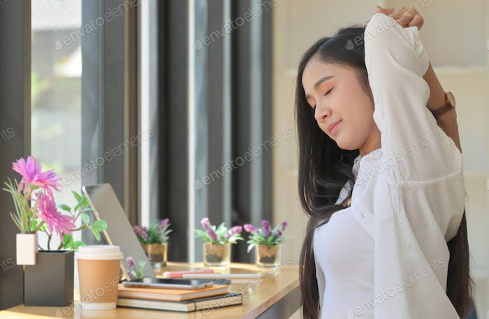 Asian women sit in the workspace and stretch their arms to relax during an online meeting.