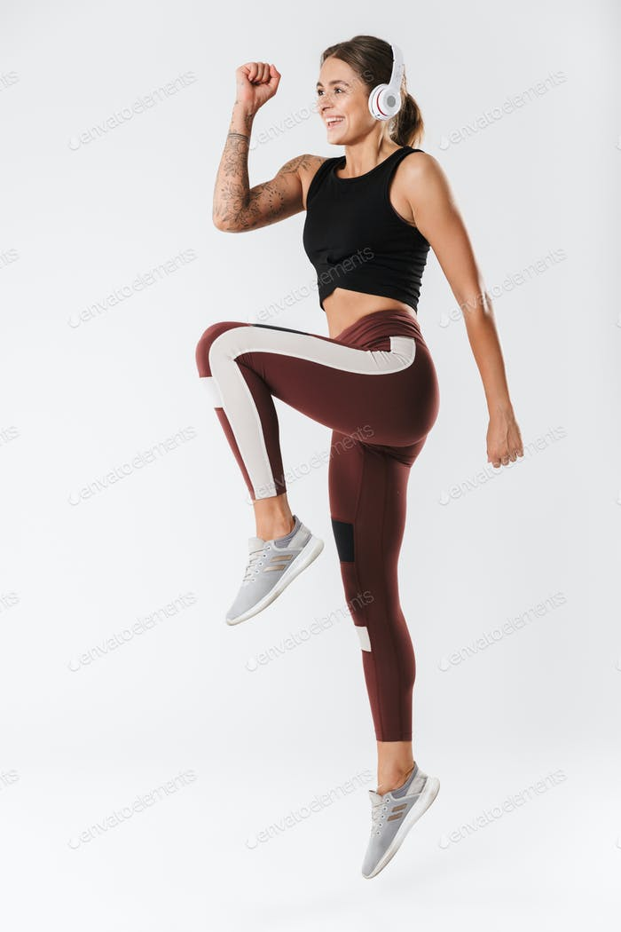 Attractive young fit sportsgirl standing isolated