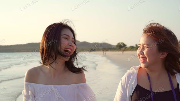 Asian lesbian couple walking on beach.