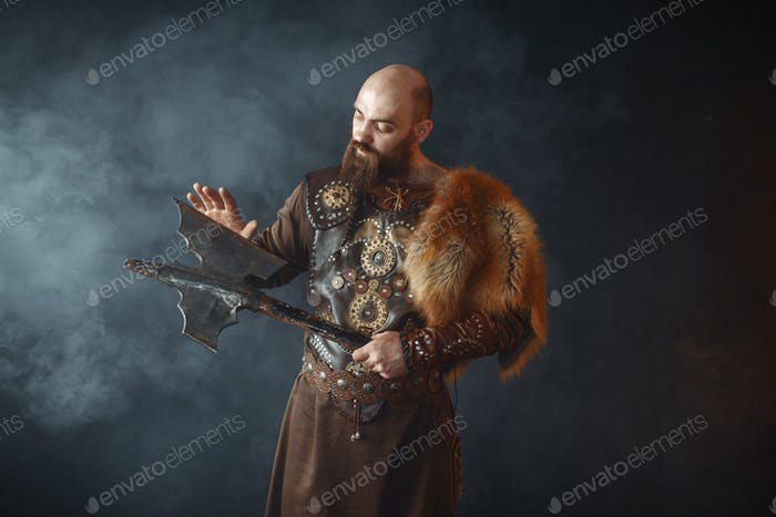 Bearded viking touches the axe blade