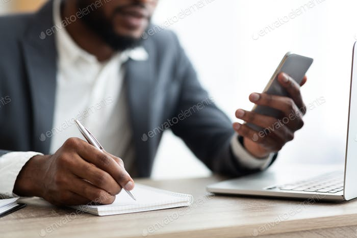 Thumbnail for African American employer using smartphone and taking notes in office