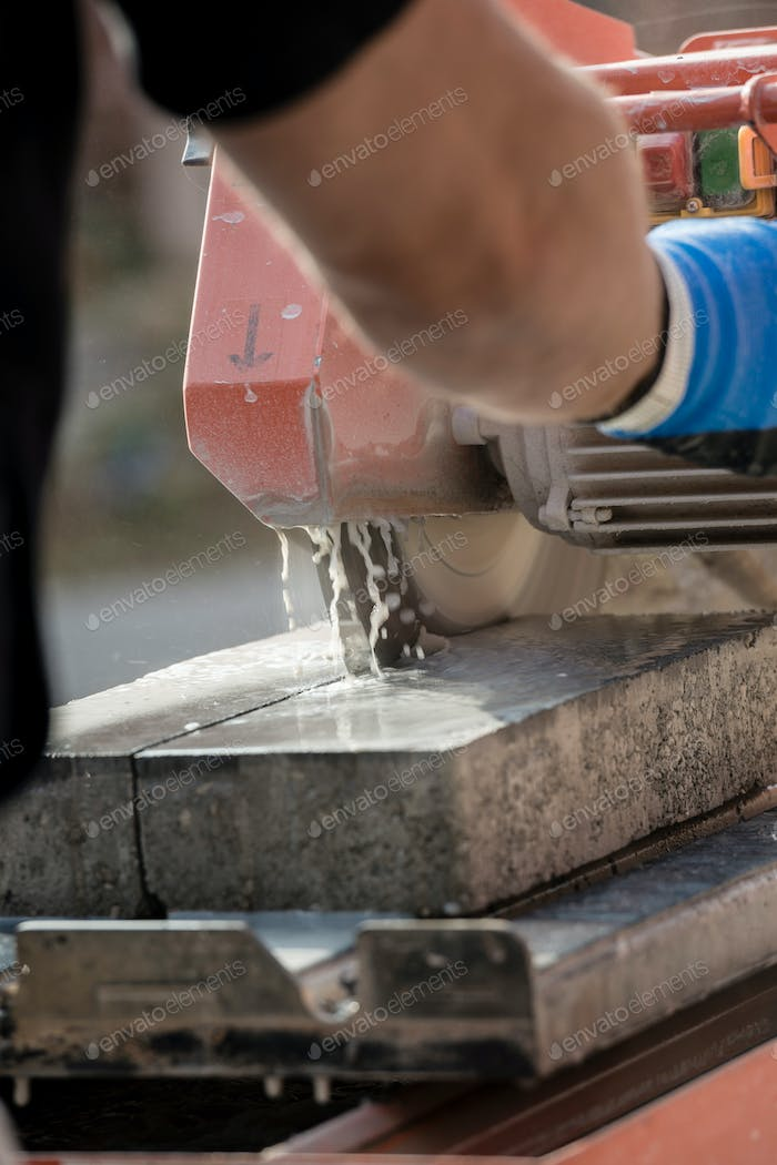 Workman using an angle grinder to cut a concrete block in a rear view