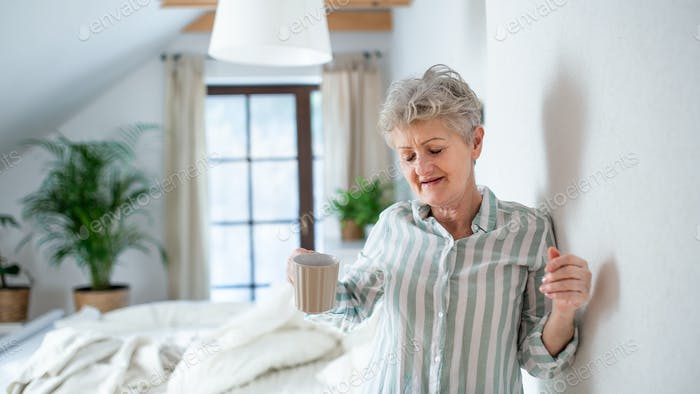 Senior woman in bed at home getting up in the morning