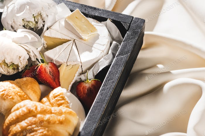 French Breakfast With Croissant, Camembert, Strawberries on Wooden Tray on White Cloth With Peonies