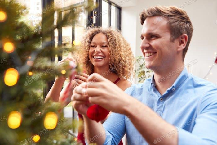 Paar At Home Hängende Dekorationen auf Weihnachtsbaum zusammen