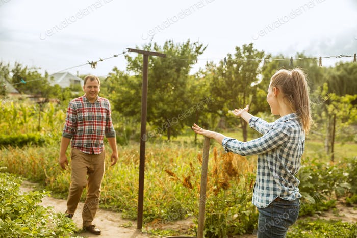 Young and happy farmer's couple at their garden in sunny day