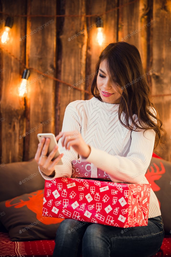 Young woman sitting on a floor using mobile phone messaging near decorated christmas wall with light