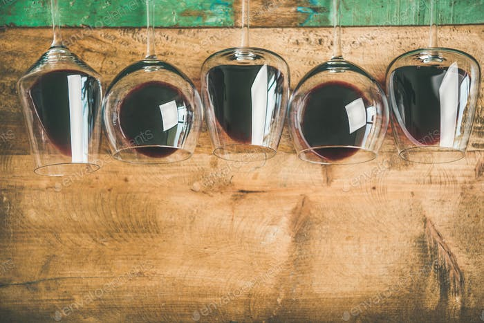 Red wine in glasses over rustic wooden background, copy space