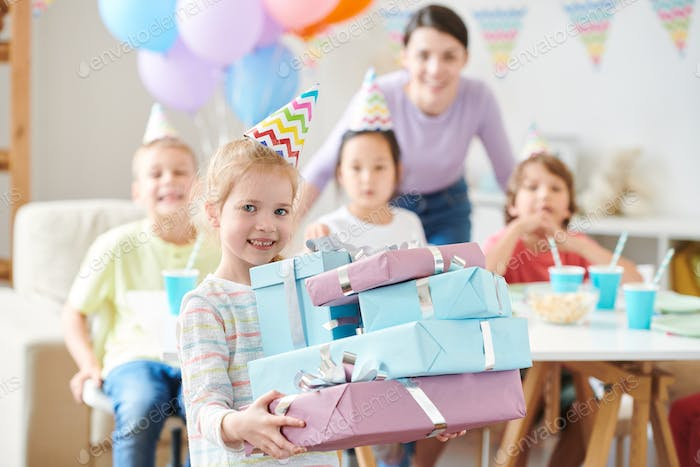 Cute blonde little girl with birthday gifts standing in front of camera