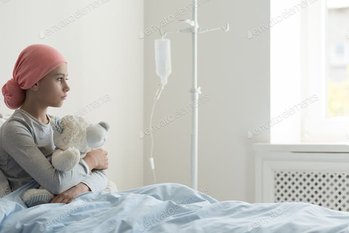 Lonely sick girl wearing headscarf and hugging plush toy in the