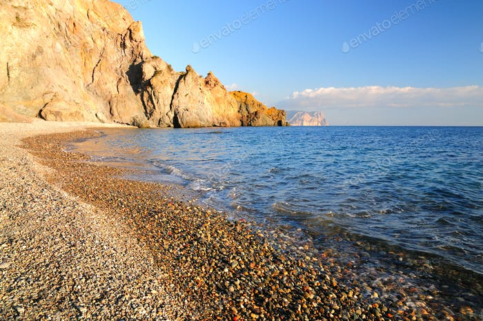 Rocky beach is washed by calm sea waves