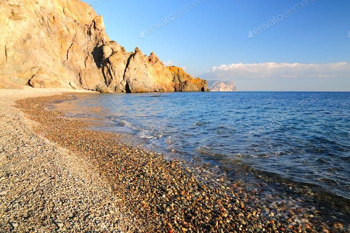 Felsigen Strand wird von ruhigen Meereswellen gewaschen
