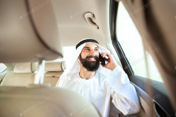 Arabian saudi businessman working in his car
