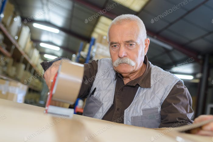 Senior man sealing cardboard box with a tape dispenser