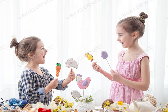 Two little girls decorate a festive cake for the Easter holiday.