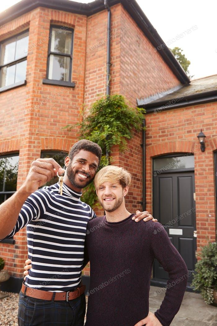 Porträt von aufgeregt Homosexuell männlich paar stehend außerhalb neue Hause halten Schlüssel auf Umzug Tag zusammen