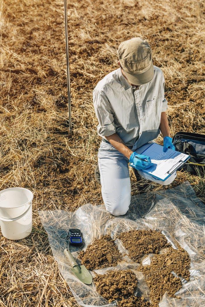 Bodentest. weiblich Agronomist nimmt Notizen im Feld