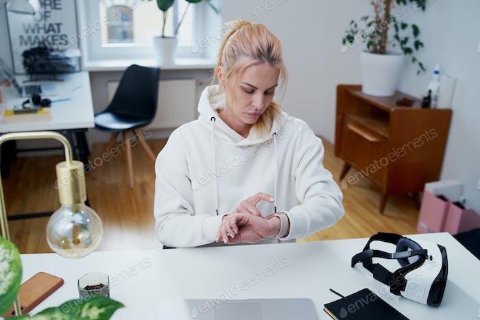 Beschäftigte Geschäftsfrau überprüft die Zeit an ihren Uhren im Amt