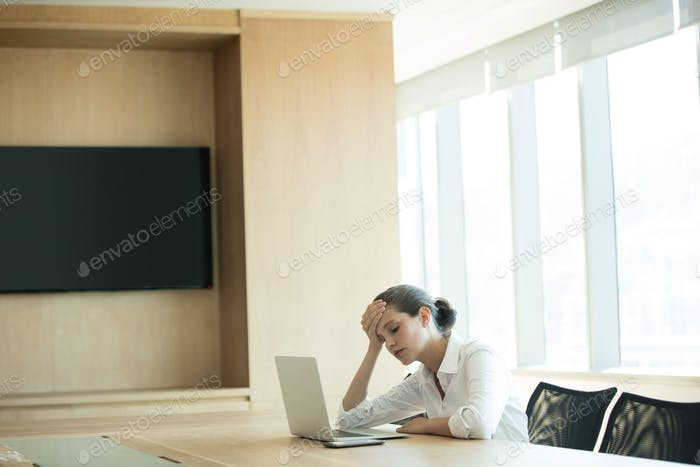 Worried businesswoman using laptop in conference room