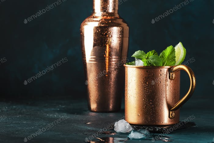 Moscow mule cocktail in copper mug with lime, ginger beer, vodka and mint