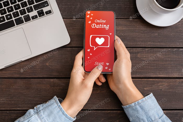 Close Up Of Woman's Hands Downloading Dating App On Smartphone