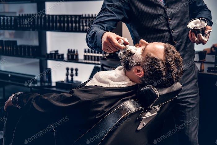 Парикмахер наносит пена для бритья