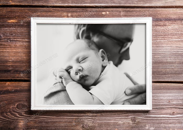 Picture of father holding his baby. Wooden background.