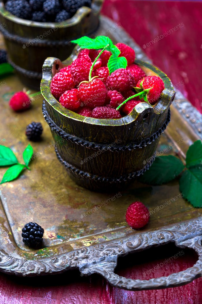 Red raspberry with leaf in a basket on vintage metal tray. Close up.