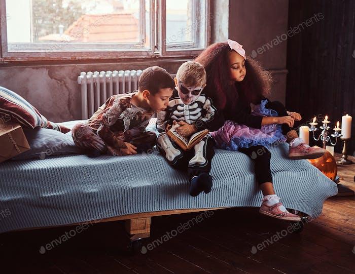 Drei multirassische Kinder in gruseligen Kostümen lesen Horrorgeschichten sitzen auf dem Bett in einem alten Haus.
