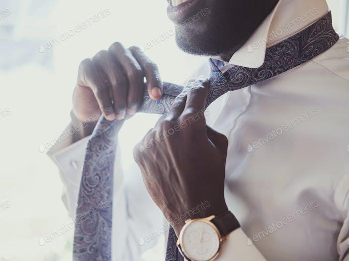 Elegant man is dressing up near window
