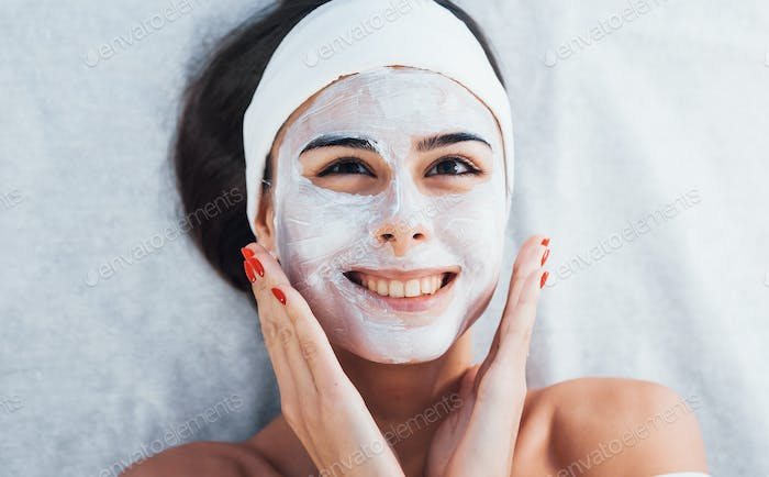 Happy woman that lying down in spa salon and have face cleaning procedure