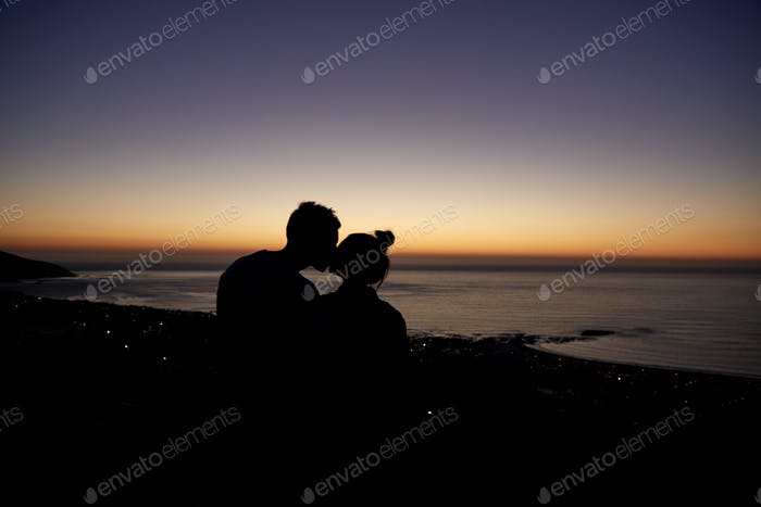 Couple kissing by the sea at sunset on a beach, silhouette