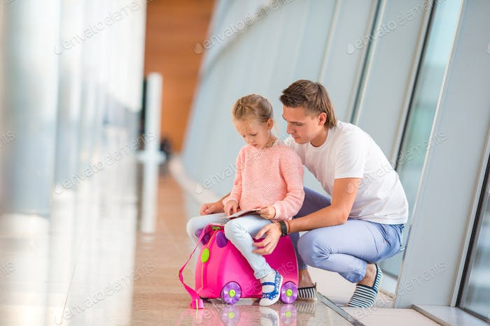 Happy dada and little girl with boarding pass at airport terminal waiting the flight