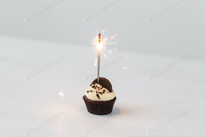 Food, holidays, happy birthday, bakery and desserts concept - delicious cupcake with sparkler on