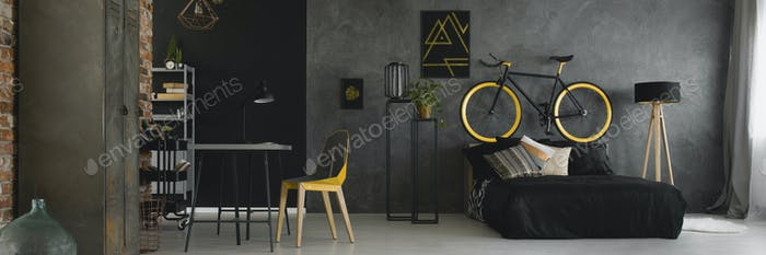 Dark studio flat interior with textured grey wall, black and yel