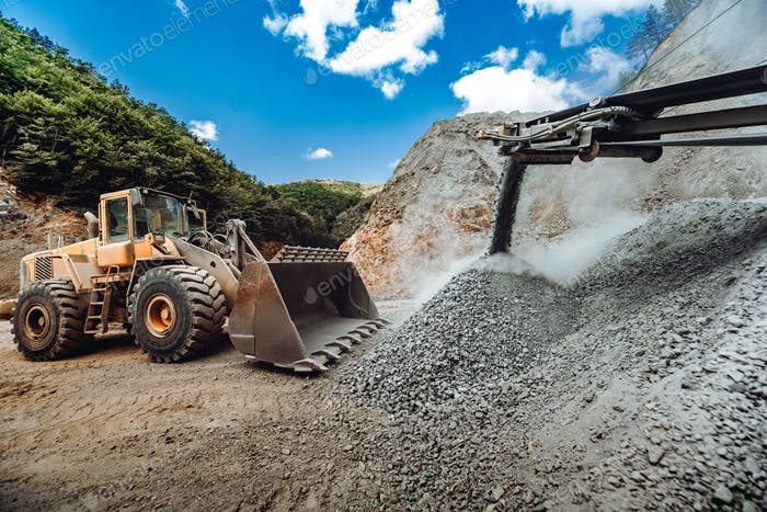 Heavy duty wheel loader bulldozer loading granite rock or ore at crushing and sorting plant