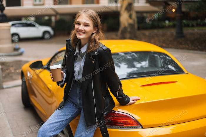 Beautiful smiling girl in leather jacket leaning on yellow sport