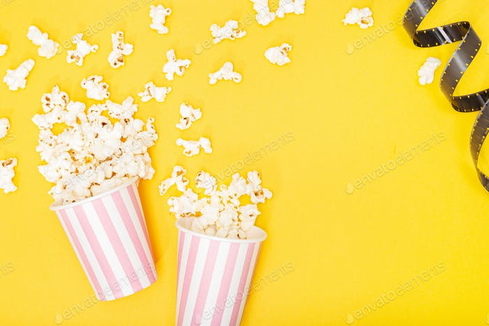 Popcorn bucket and film strip on yellow background