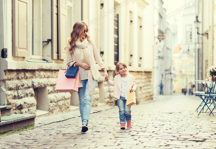 happy mother and child with shopping bags in city