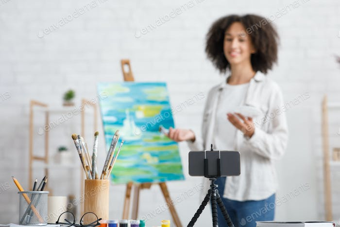 Smartphone, glasses and paint brushes. Focus on gadget and tools for art lesson