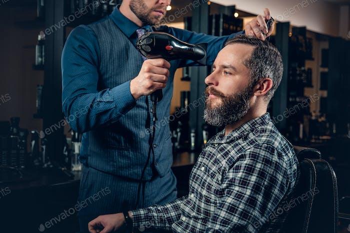 Парикмахер сушки мужских волос с феном в салоне.