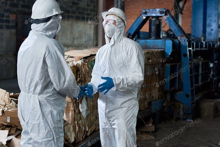 Arbeiter in Gefahrgutanzügen, die in der Fabrik kommunizieren