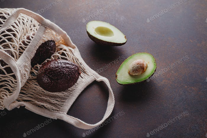 Avocado hass in an eco net bag on a table
