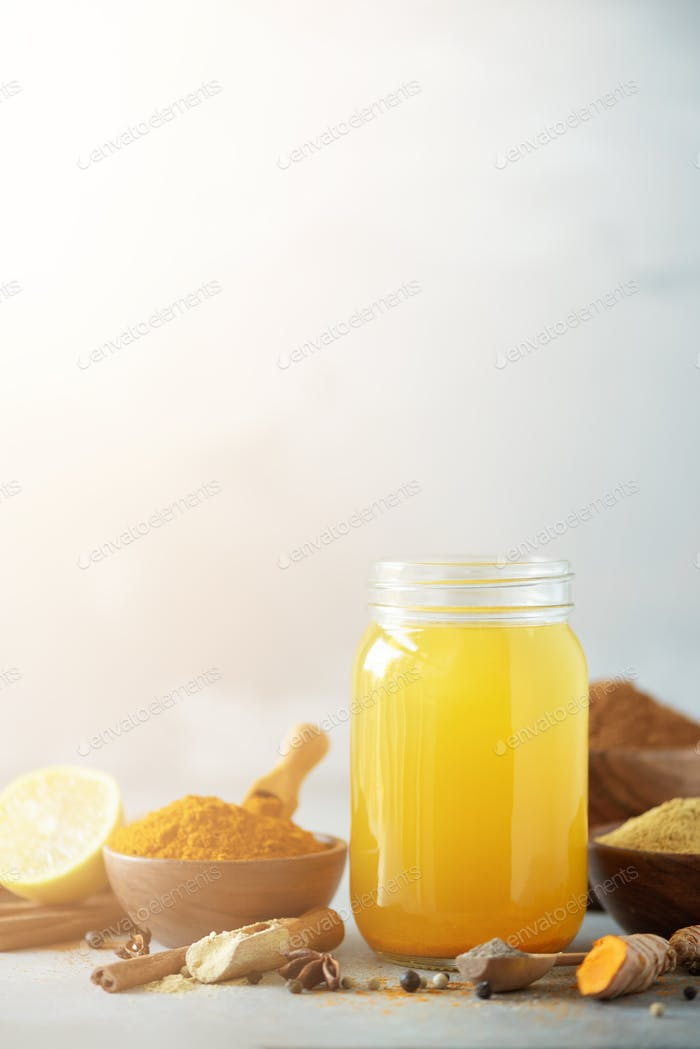 Spicy healthy turmeric drink with lemon, ginger, black pepper on grey background. Vegan hot drink
